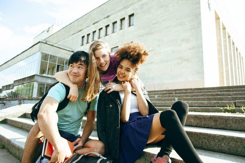Gruppo sveglio di teenages alla costruzione dell'universit? con i huggings dei libri, stile di vita degli studenti di nazioni di  fotografia stock