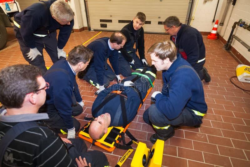 Gruppo tedesco del pompiere in un esercizio con danneggiato in una barella fotografia stock