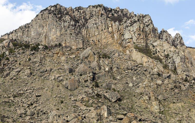 Gruppo windblown della parete di pietra della roccia della montagna alto di ciottoli al piede di una passeggiata pericolosa di sa immagine stock