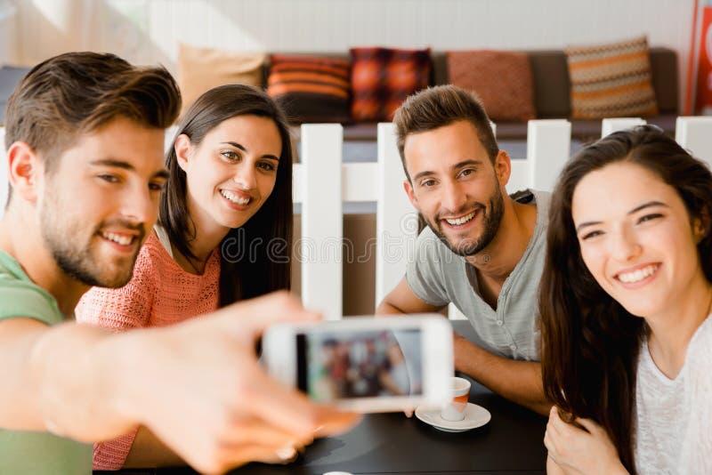 Gruppselfie på coffee shop fotografering för bildbyråer