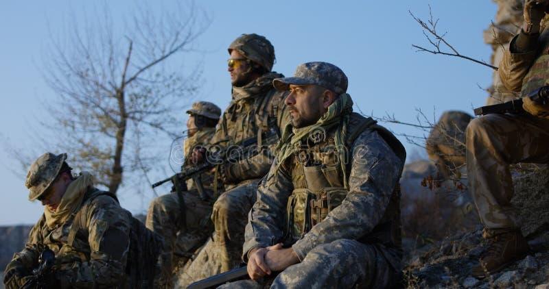 Gruppsoldater som tar ett avbrott under en anfall fotografering för bildbyråer