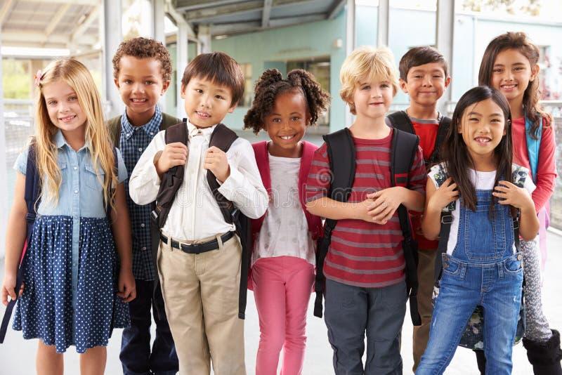 Gruppstående av grundskolaungar i skolakorridor royaltyfria bilder