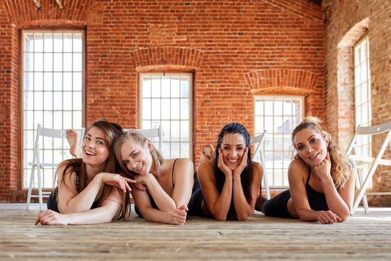 Gruppstående av unga sportiga upphetsade härliga flickor med övningsmats som står bredvid den vita väggen som skrattar och arkivbilder