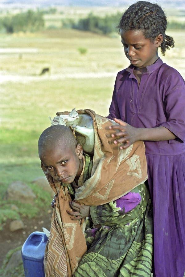 Gruppståendeflickor som kånkar dricksvatten, Etiopien arkivbilder