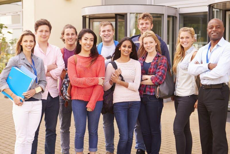 Gruppståenden av högskolestudenter med handleder royaltyfri fotografi