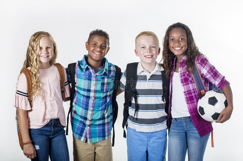 Gruppståenden av pre-tonåringen skolan lurar att le på en vit bakgrund royaltyfri foto