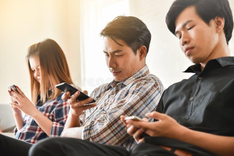 Gruppstudenter använder mobiltelefoner arkivfoton