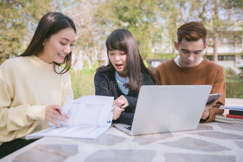 Gruppstudenter ler och har gyckel som det hjälper också att dela idéer I royaltyfri foto