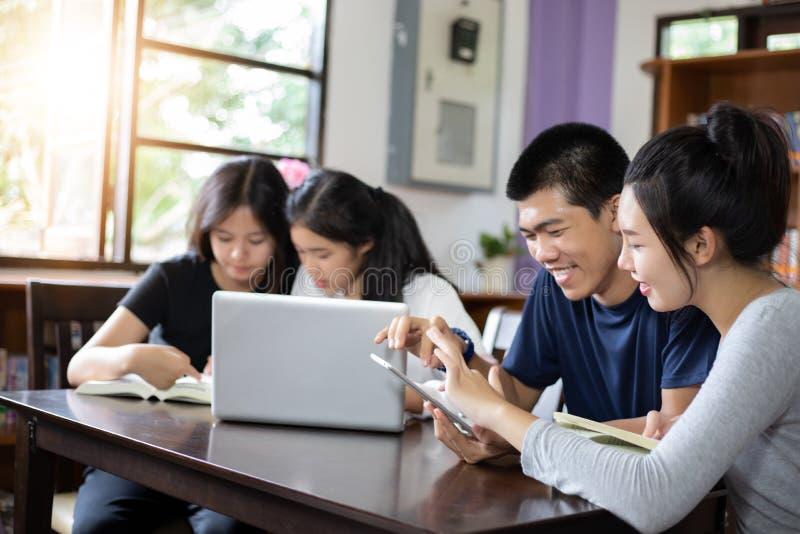Gruppstudenter ler och har roligt och att använda minnestavlan som det hjälper också att dela idéer i arbetet och projektet Och g royaltyfri fotografi