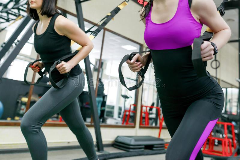 Grupputbildning med konditionöglor i idrottshallen, två unga attraktiva idrottsman nenkvinnor som gör crossfit med remsystemet Sp royaltyfri foto