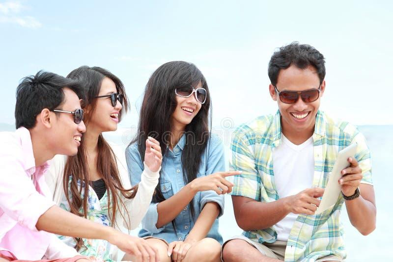 Gruppvänner som tycker om stranden, semestrar samman med minnestavlaPC arkivfoton