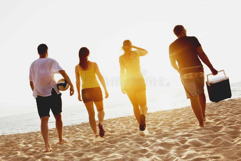 Grupy cztery przyjaciele wyrzucać na brzeg picknik zmierzchu morze obraz stock
