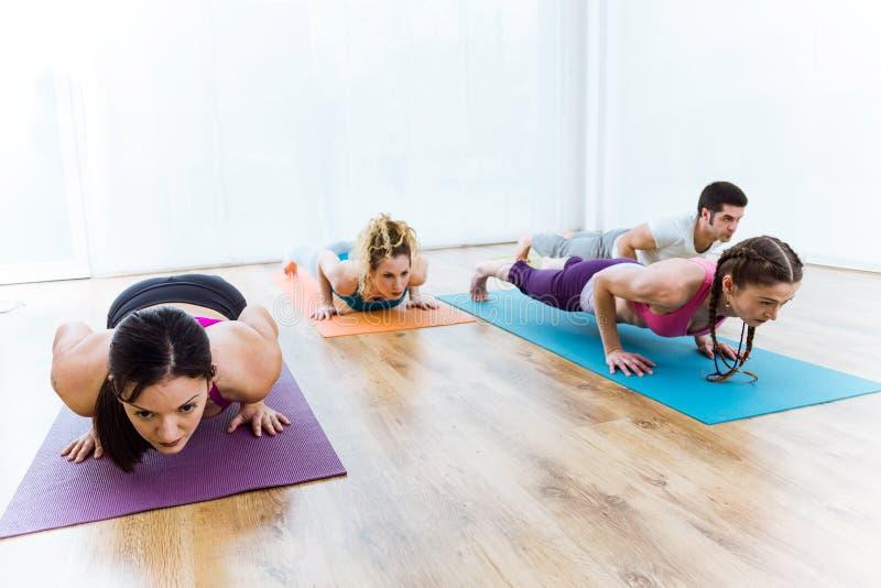 Grupy ludzi ćwiczy joga w domu Chaturanga dandasana po zdjęcia royalty free