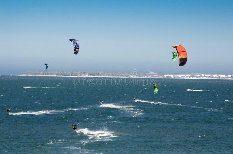 Grupy ludzi krańcowa akcja skakać nad woda morska z kitesurfing deską w zielonym kolorze przy Brighton Le Piasek plażą zdjęcia royalty free