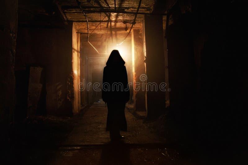 Gruseliges Schattenbild im Dunkelheit verlassenen Gebäude Horror über Wahnsinnigekonzept stockbild