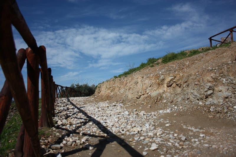 Grusväg i bygden på en härlig vårdag ett trästaket på en sida och en härlig blå himmel royaltyfri foto
