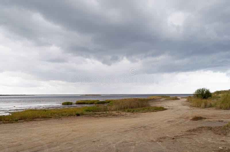 Grusväg längs havskostnaden, stormmoln royaltyfri foto