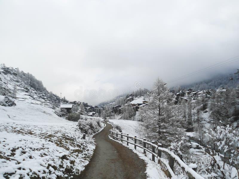 Grusväg längs trästaketet på utkant av den alpina semesterorten arkivfoto