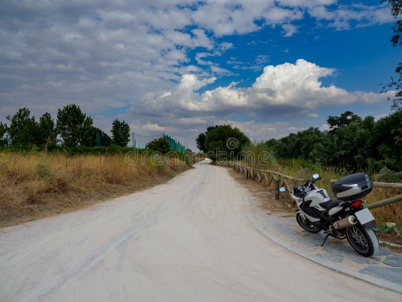 Grusväg med torr gul vegetation och gröna träd, med en parkerad motorcykel arkivfoto