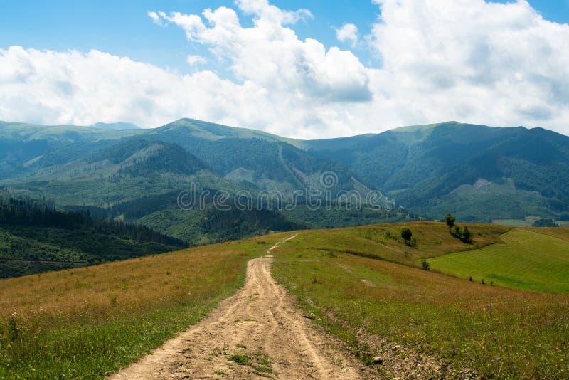 Grusväg mot landskapet i de ukrainska Carpathiansna royaltyfri fotografi