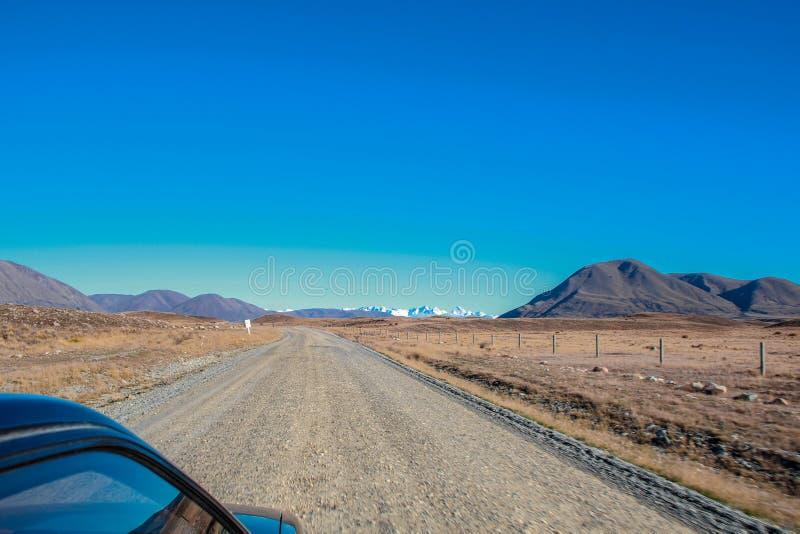 Grusväg som leder till berg i Ashburton sjöområdet, södra ö, Nya Zeeland royaltyfria foton