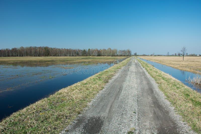 Grusväg till och med översvämmad fält, horisont och himmel arkivbild