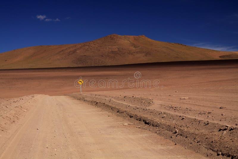 Grusväg till och med den röda ofruktbara marken som kontrasterar med djupblå molnfri himmel, borttappat gult tecken som visar vän arkivbilder