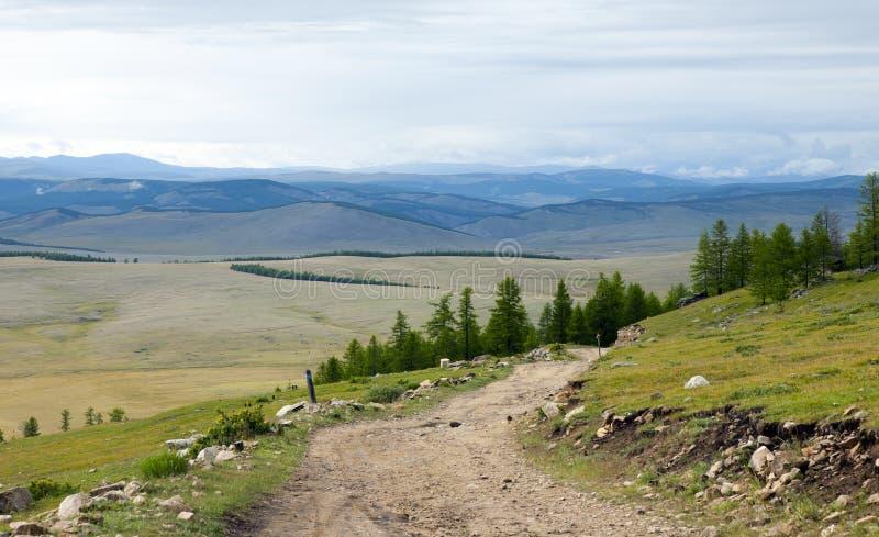 Grusväg till och med nordliga Mongoliet berg fotografering för bildbyråer
