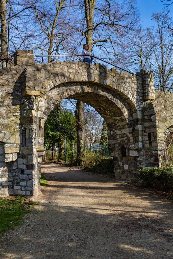 Grusvägen och bågen av en gammal stenbro med en kvinna på den, en grusväg i Proosdijen parkerar royaltyfri bild