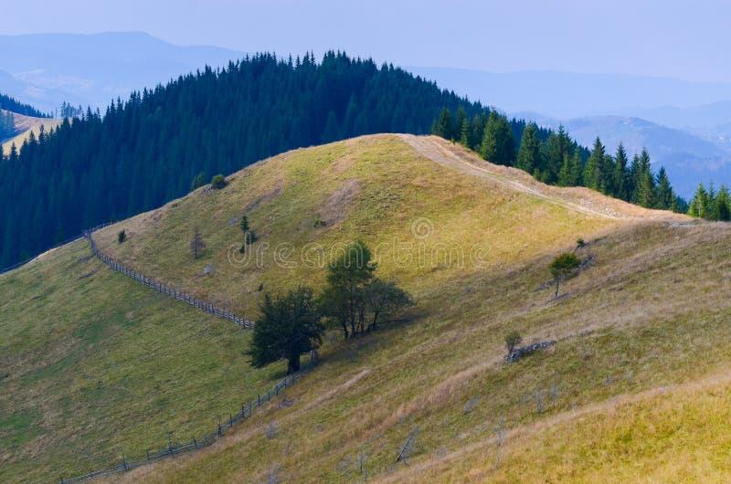 Grusväghöjdpunkt i bergen som går ner till byn i dalen arkivfoton
