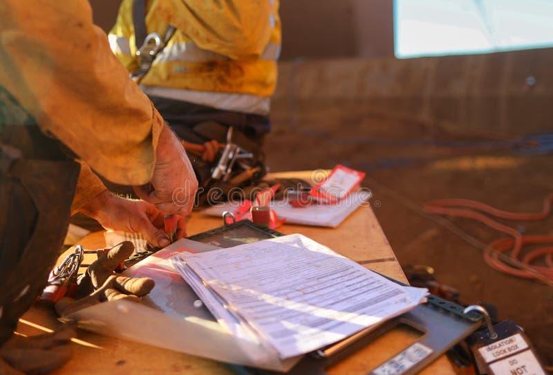Gruvarbetare som tar bort låset för personalsäkerhetsisolering och tecknet av arbetet på höjdtillståndet på isoleringslåsasken ef royaltyfria bilder
