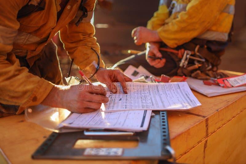 Gruvarbetare som tar bort låset för personalsäkerhetsisolering och tecknet av arbetet på höjdtillståndet på isoleringslåsasken ef arkivbild