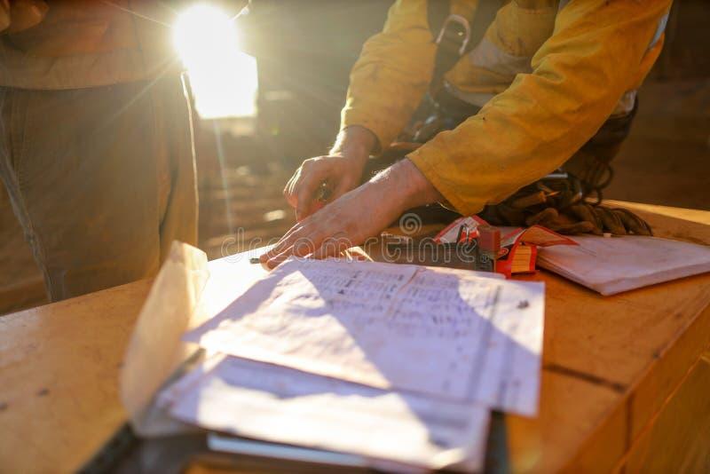Gruvarbetare som tar bort låset för personalsäkerhetsisolering och tecknet av arbetstillståndet på isoleringslåsasken efter avslu royaltyfri bild