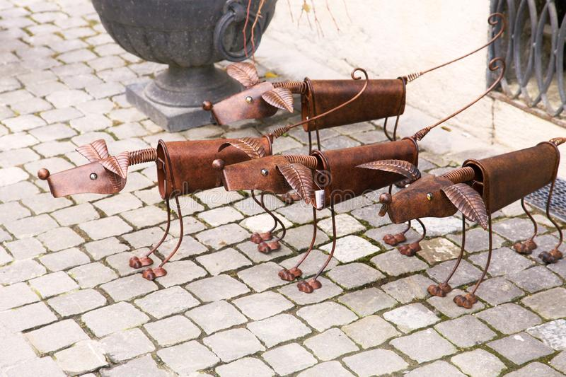 Gruyer, Switzerland - May 2016: The group of small funny sculptures of dogs made from tin settled on the pavement, outdoors. royalty free stock photos