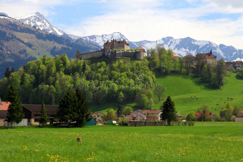 Gruyere Castle and Alps, Switzerland. Beautiful landscape with Gruyere Castle, fields and Alps Mountains in the background, Switzerland stock image