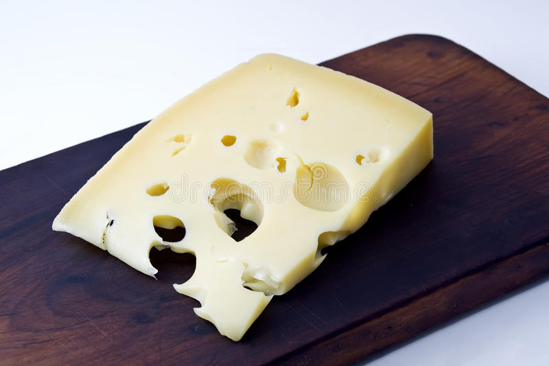 Gruyere cheese. A piece of gruyere cheese over rustic table stock images