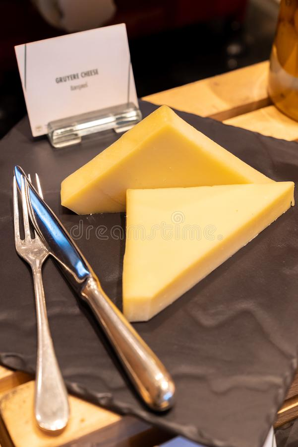 Gruyere Cheese. On black stone plate in buffet line stock photography