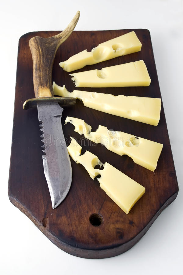 Gruyere cheese and knife. A piece of gruyere cheese over rustic table with a rustic knife royalty free stock image