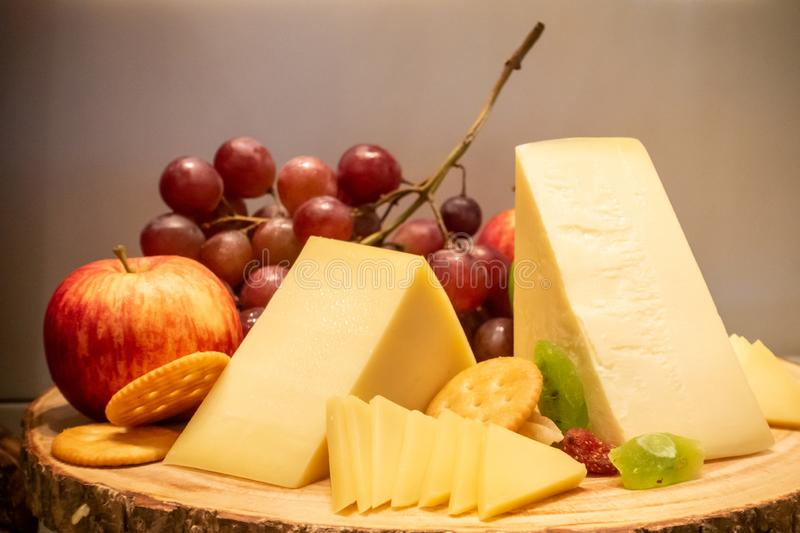 Gruyere cheese. With variety of fruit and cracker on wooden plate in buffet line royalty free stock images