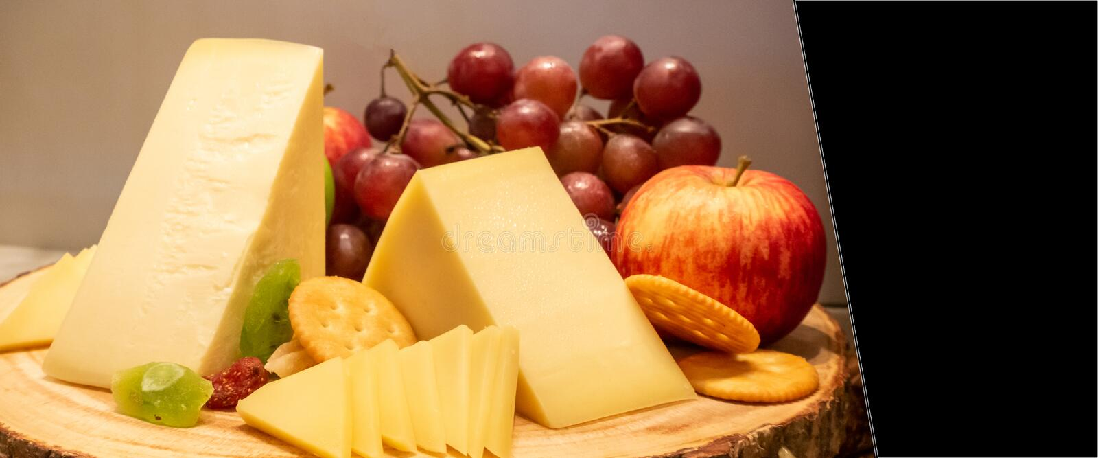 Gruyere cheese. With variety of fruit and cracker on wooden plate in buffet line, panoramic Large Leaderboard crop size stock photos