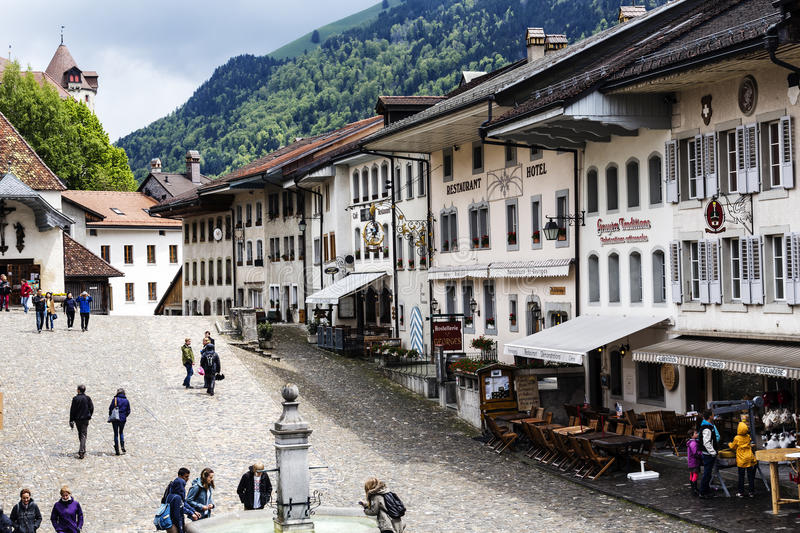 Gruyere historic Alpine city. GRUYERE - MAY 25: Unidentified tourists overlooking the market and historic buildings of Alpine city with only about 1800 citizens stock photography