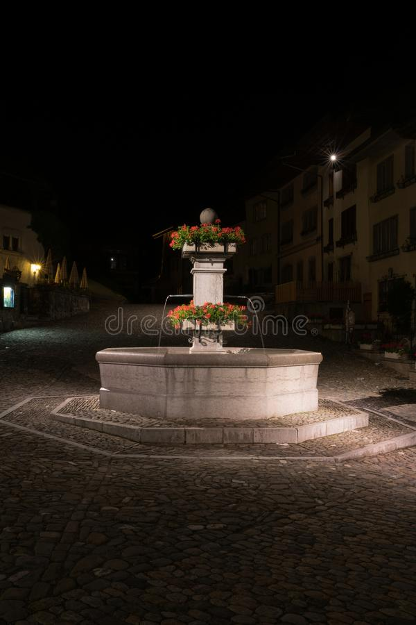 Gruyeres, VD / Switzerland - 31 May 2019: the historic medieval village of Gruyeres with the village square fountain at night stock photo