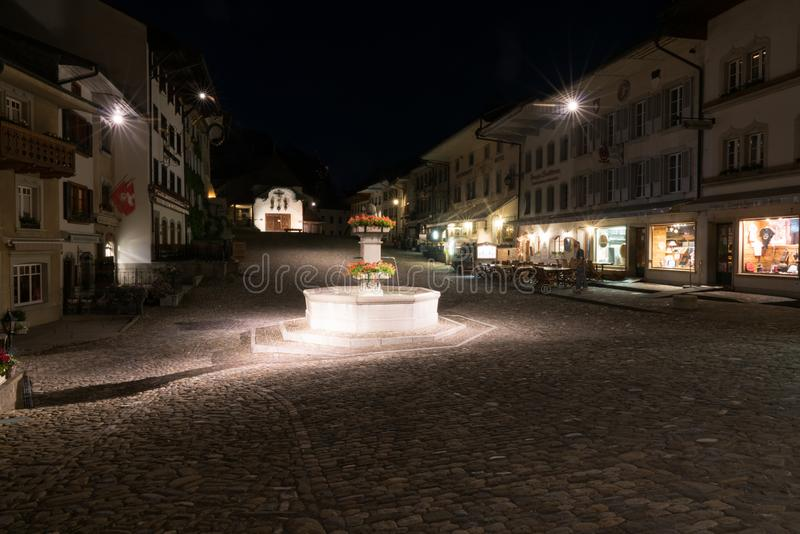 Gruyeres, VD / Switzerland - 31 May 2019: the historic medieval village of Gruyeres with the village square fountain at night stock photos