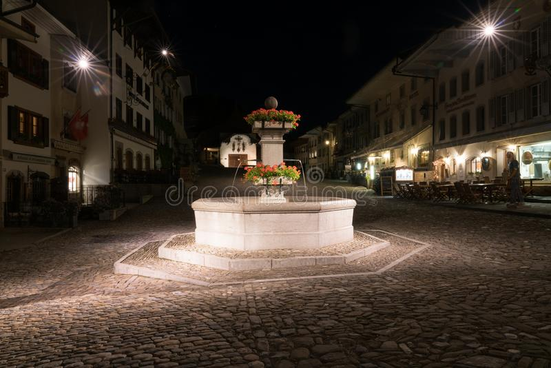 Gruyeres, VD / Switzerland - 31 May 2019: the historic medieval village of Gruyeres with the village square fountain at night royalty free stock image