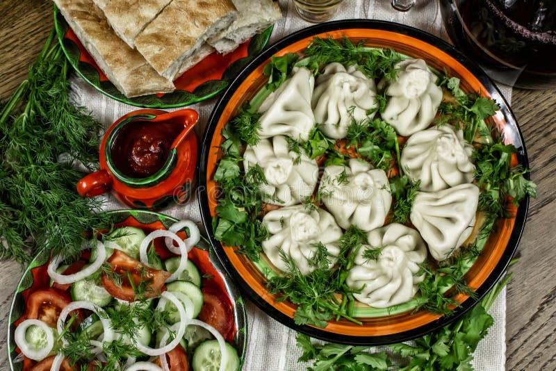 Gruzińska uczta z jedzeniem, khinkali na stole, świeże warzywa z ziołami, chleb pita i wino obraz stock