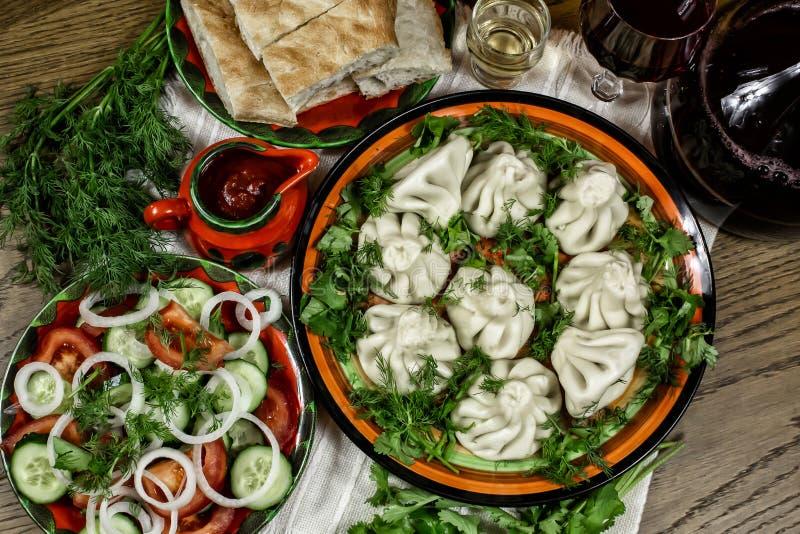 Gruzińska uczta z jedzeniem, khinkali na stole, świeże warzywa z ziołami, chleb pita i wino zdjęcie royalty free