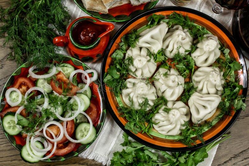 Gruzińska uczta z jedzeniem, khinkali na stole, świeże warzywa z ziołami, chleb pita i wino obraz royalty free