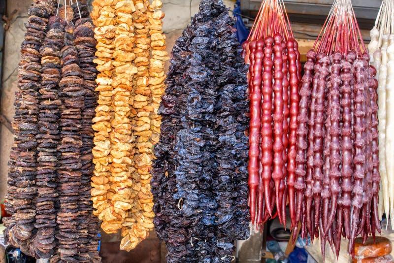 Gruzja, miejscowego rynek Sprzedaż krajowi cukierki od winogron i dokrętek owoc - «Churchkhela «, susząca - obraz royalty free