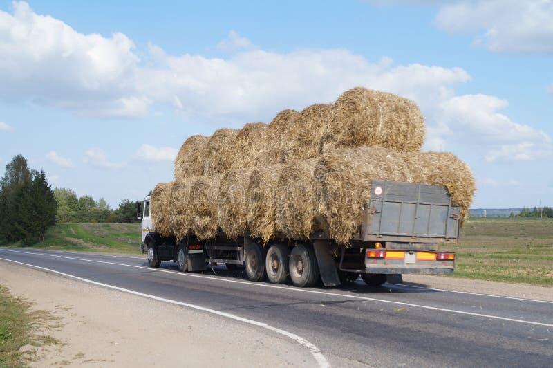 Gruzovik-测量仪用圆的大包秸杆乘驾装载了在高速公路 图库摄影