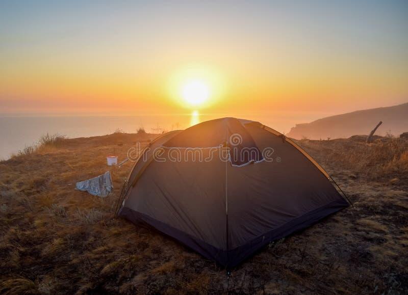 Gry över havet, soluppgång över tältet arkivbild